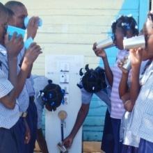 Haitianische Schulkinder in Uniform stehen beim Wasserrucksack Paul und trinken das gefiltere Wasser aus Bechern