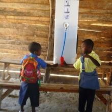Zwei haitianische Schulkinder trinken von Paul, dem Wasserrucksack