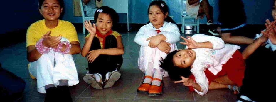 Man sieht vier kleine Kinder lachend auf dem Boden sitzen und ein Ratespiel spielen