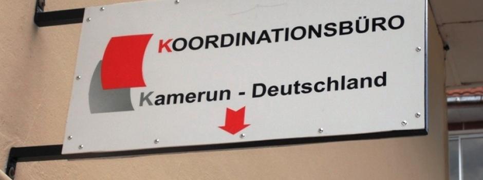Das Bild zeigt ein Hausschild, auf dem das rot-weiße Logo des kamerunischen Alumnidachverband KBK zu sehen ist