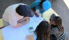 Man sieht vier ausländische Studierende aus der Vogelperspektive an einem Konzeptpapier in Gruppenarbeit sitzen